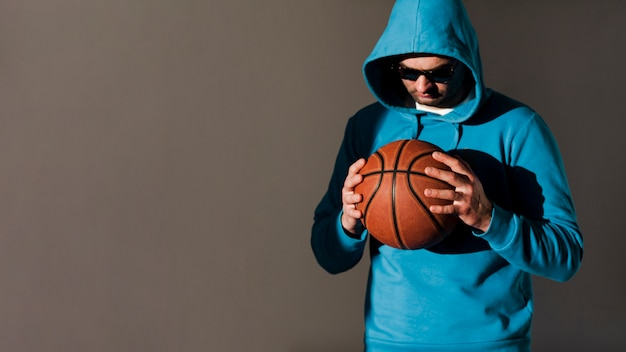 Front view of man with hoodie holding basketball with copy space