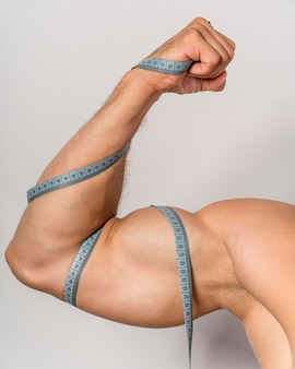 Front view of man with measuring tape over bicep and arm