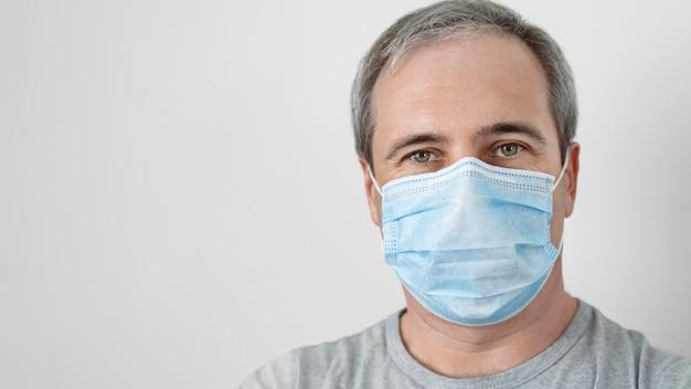 Vista frontale dell'uomo con maschera medica dopo la vaccinazione