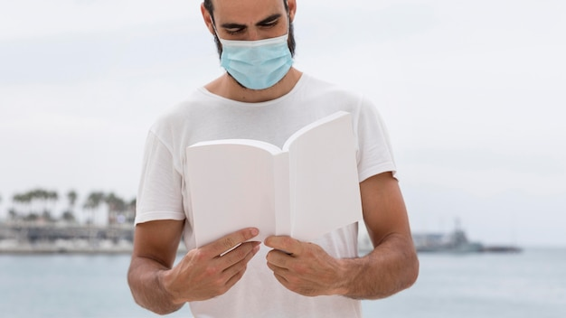 Front view of man with medical mask by the lake reading book