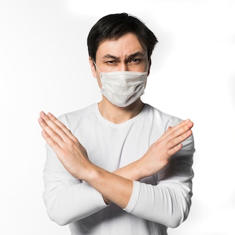 Front view of man with medical mask making x sign with arms