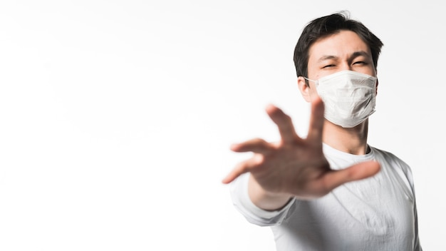 Front view of man with medical mask reaching for something