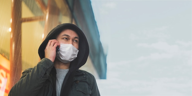 Front view of man with medical mask talking on the phone