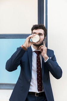 Front view man with phone drinking coffee