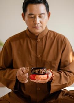 Vista frontale dell'uomo con le campane tibetane