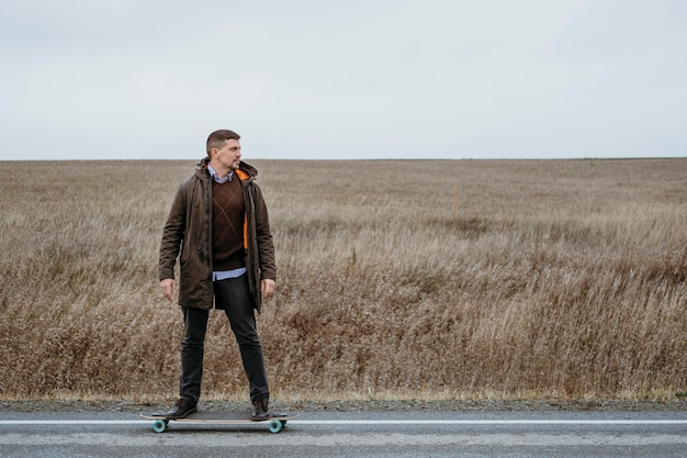 Front view of man with skateboard on the road