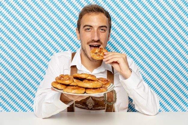 Front view of man with soft pretzels plate
