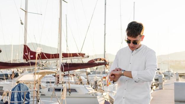 Vista frontale dell'uomo con gli occhiali da sole al porto turistico guardando l'orologio