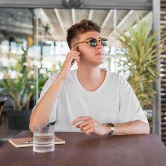 Vista frontale dell'uomo con gli occhiali da sole parlando al telefono al pub