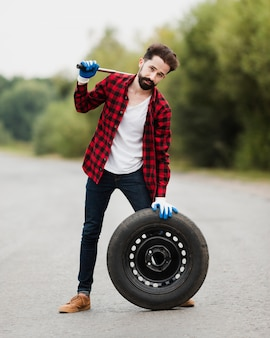 Front view of man with wrench and tire