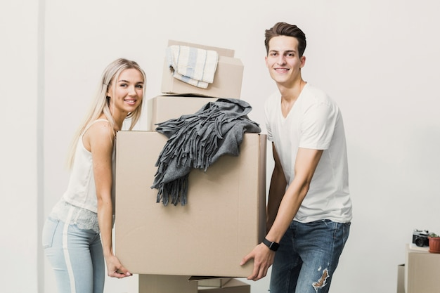 Front view man and woman carrying box