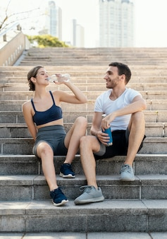 Front view of man and woman drinking water outdoors while exercising