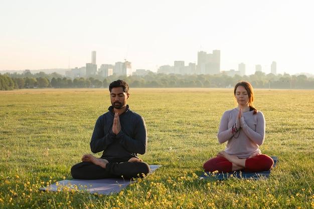 Vista frontale dell'uomo e della donna che meditano all'aperto su stuoie di yoga