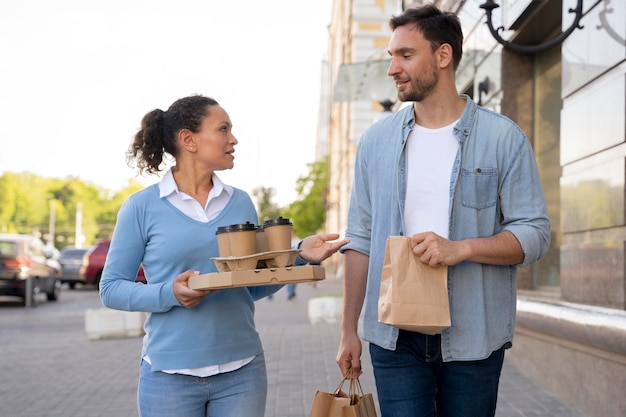 Front view of man and woman outdoors with takeaway food