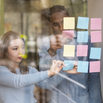 Front view of man and woman putting sticky notes on office window