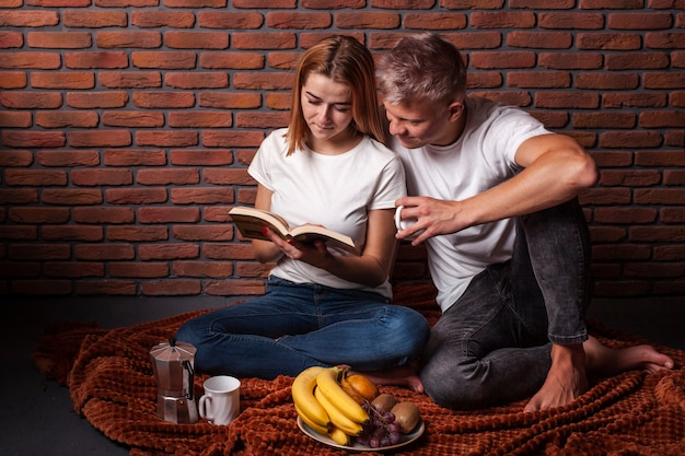 Front view man and woman reading together a book