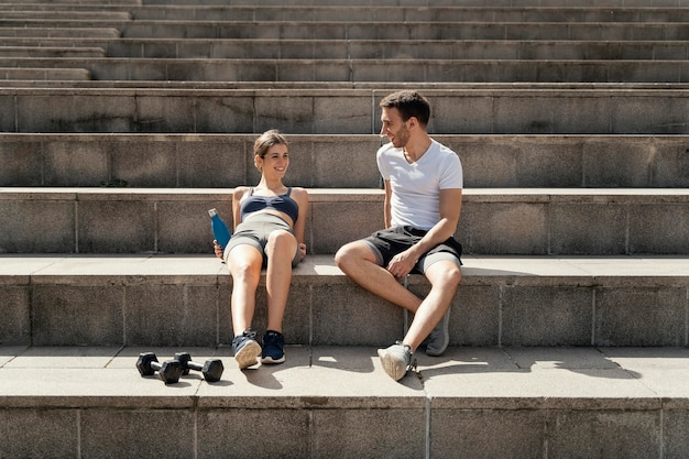 Front view of man and woman resting on steps while exercising