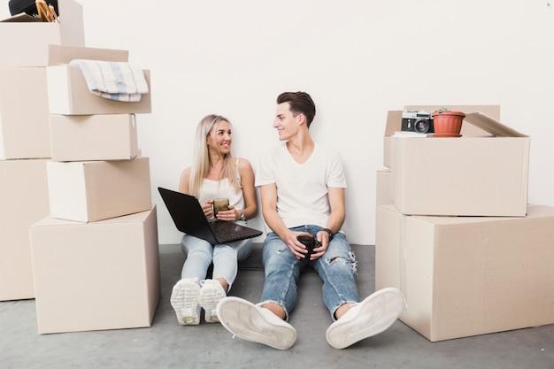 Vista frontale uomo e donna seduta sul pavimento