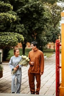 Vista frontale di un uomo e di una donna al tempio con incenso e bouquet di fiori