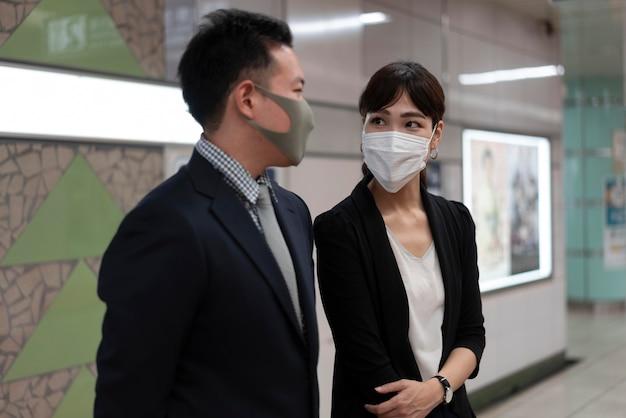 Vista frontale dell'uomo e della donna che indossa la maschera per il viso