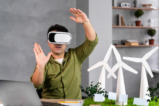 Front view of man working on an eco-friendly wind power project and using virtual reality headset