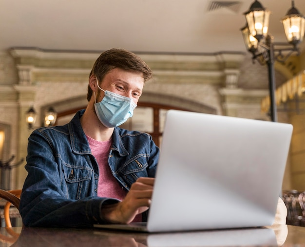 Front view man working indoors while wearing a face mask
