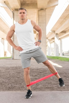 Front view man working out with a stretching band