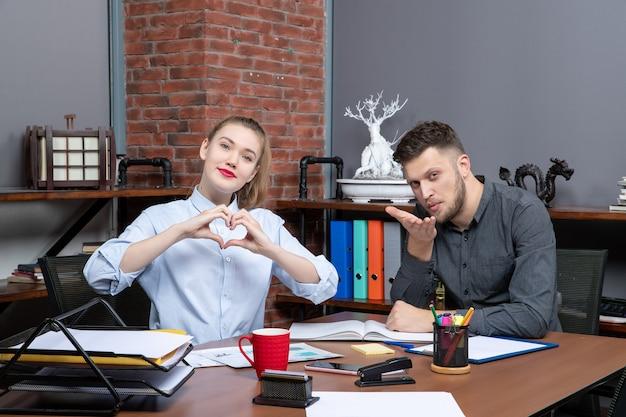 Vista frontale del team di gestione seduto al tavolo in posa per la telecamera in ufficio