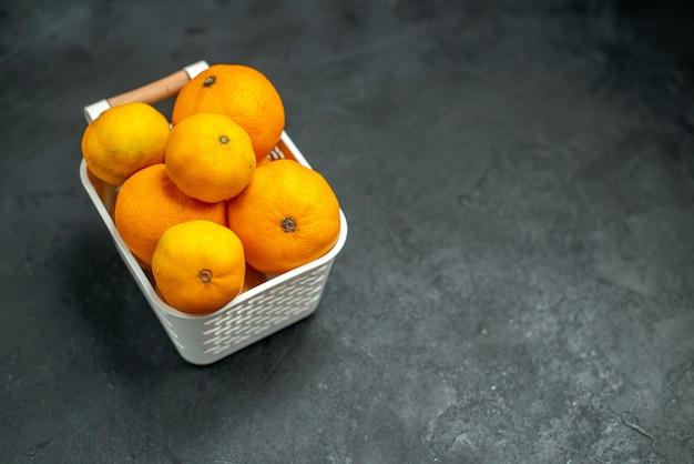 어두운 배경 여유 공간에 플라스틱 바구니에 있는 전면 보기 만다린 및 오렌지