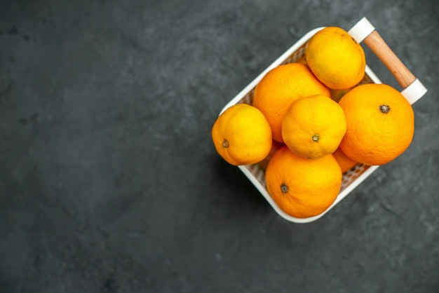 暗い背景の空きスペースにプラスチックバスケットの正面図みかんとオレンジ