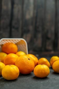 暗い自由空間のplastcバスケットから散らばっている正面図みかんとオレンジ