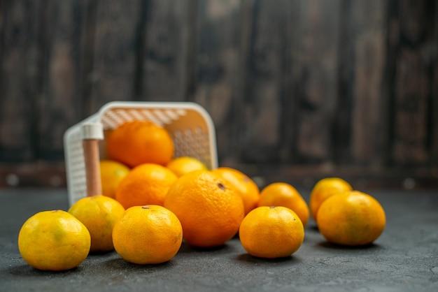 暗い背景の空きスペースにプラスチックバスケットから散らばっている正面図みかんとオレンジ