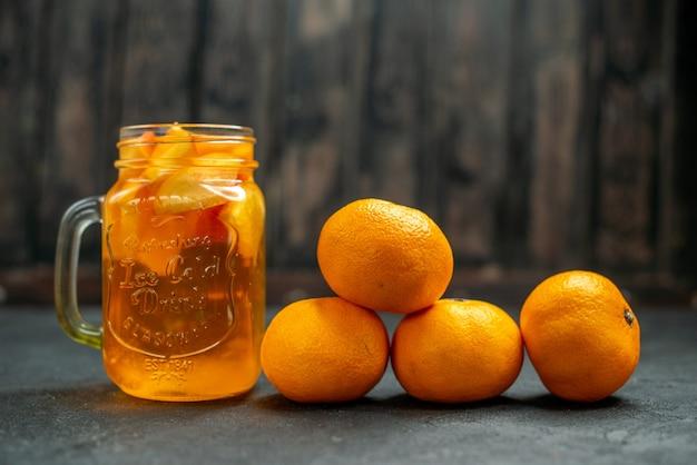 Вид спереди коктейль из мандаринов на темном фоне свободного пространства
