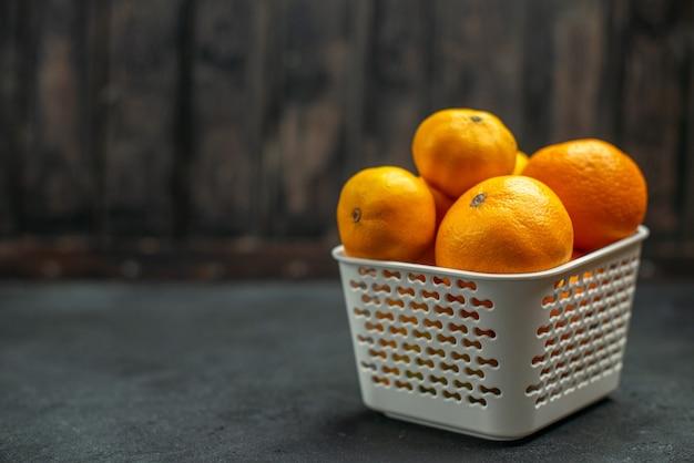 Mandarini e arance di vista frontale in cestino di plastica su spazio libero del fondo scuro