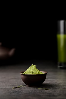 Front view of matcha tea powder in bowl with copy space