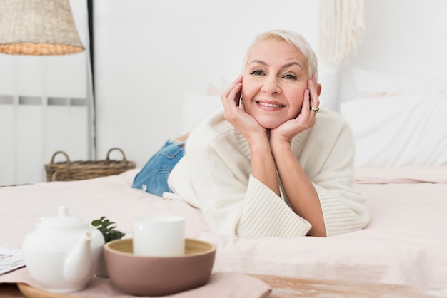 Front view of mature happy woman smiling and posing in bed