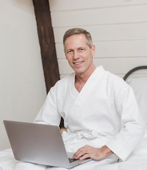 Front view mature man holding his laptop in bed