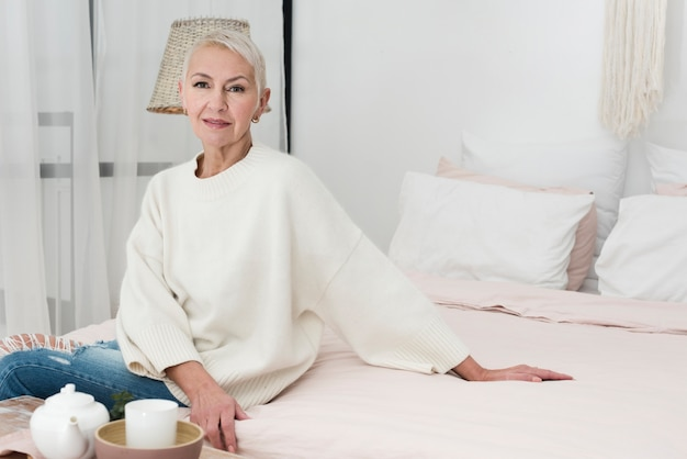 Front view of mature smiley woman posing in bed with copy space