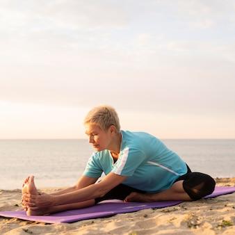 Vista frontale della donna matura che fa yoga sulla spiaggia