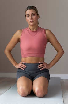 Front view mature woman sitting on a yoga mat