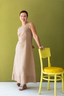 Front view mature woman with yellow chair