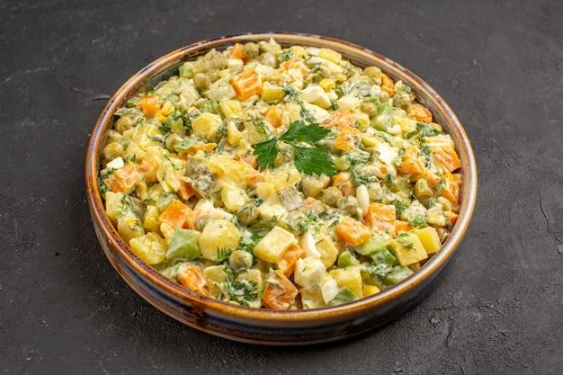 Vista frontale dell'insalata di maionese con diverse verdure sulla superficie scura