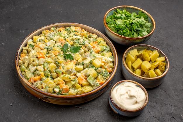 Vista frontale dell'insalata di verdure mayyonaise sulla superficie scura