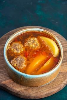 紺色の壁に丸皿の中にジャガイモが入った正面図のミートボールスープフードスープ肉料理ディナー野菜