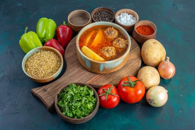 スライスしたジャガイモが入った正面図のミートボールスープと紺色の壁に新鮮な野菜が入ったフードスープ肉料理ディナー野菜