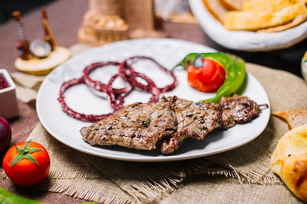 Front view meat basturma kebab with tomato and hot pepper on the grill with onion in sumac