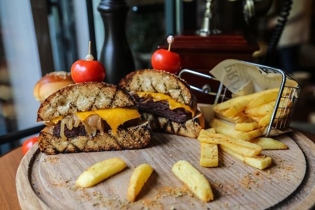 Вид спереди половинки мясного бургера с помидорами и картофелем фри со специями на подставке