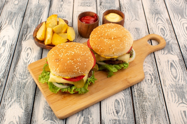 A front view meat burger with cheese and green salad potatoes and dips on the wooden table and grey table