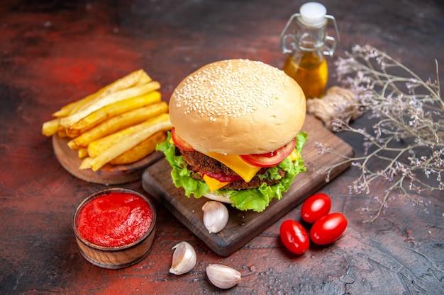 暗い背景にチーズサラダとトマトの正面図ミートバーガー
