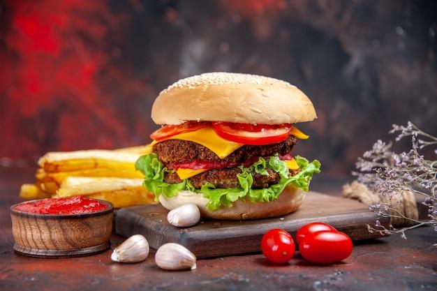 Мясной бургер, вид спереди, сырный салат и помидоры на темном столе